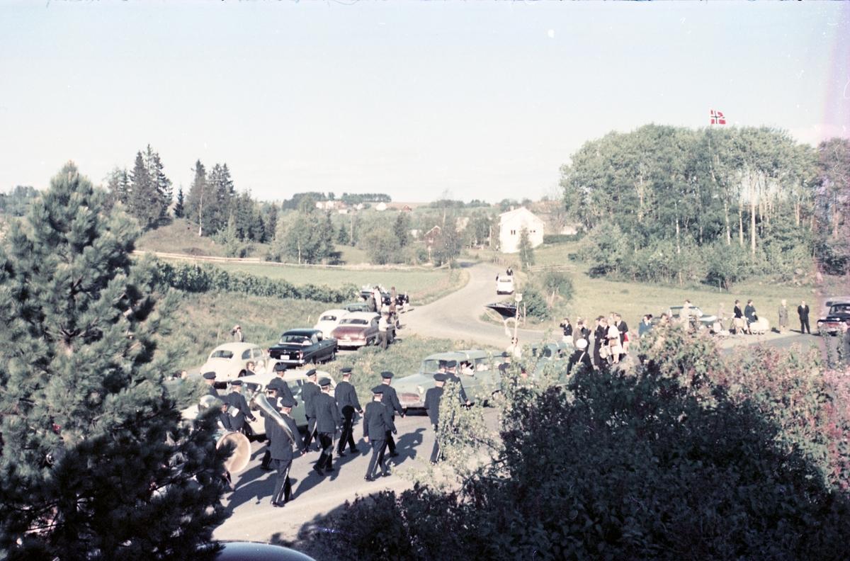 Serie på 16 bilder trolig fra Sangens og Musikkens Dag i Østre Toten, muligens 1958. Bildene er tatt i retning Brunsberg fra fotografens eiendom Odberg på Kraby, der forskjellige korps og kor deffilerer forbi.