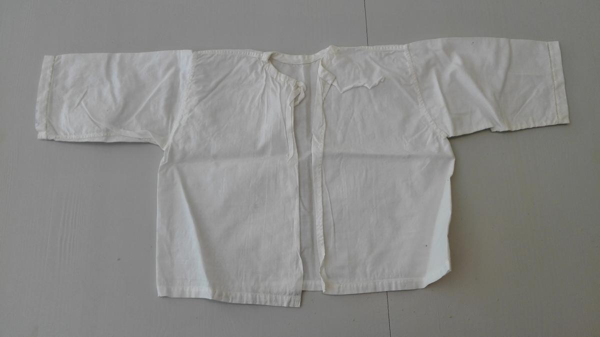 1 spebarnskjorte.  Spebarnskjorte med opning i ryggen. Isett langt erme. Tilhøyrande rykt krage. Holsaum på krage og i nedkant av bol og erme. Sydd på kurs.