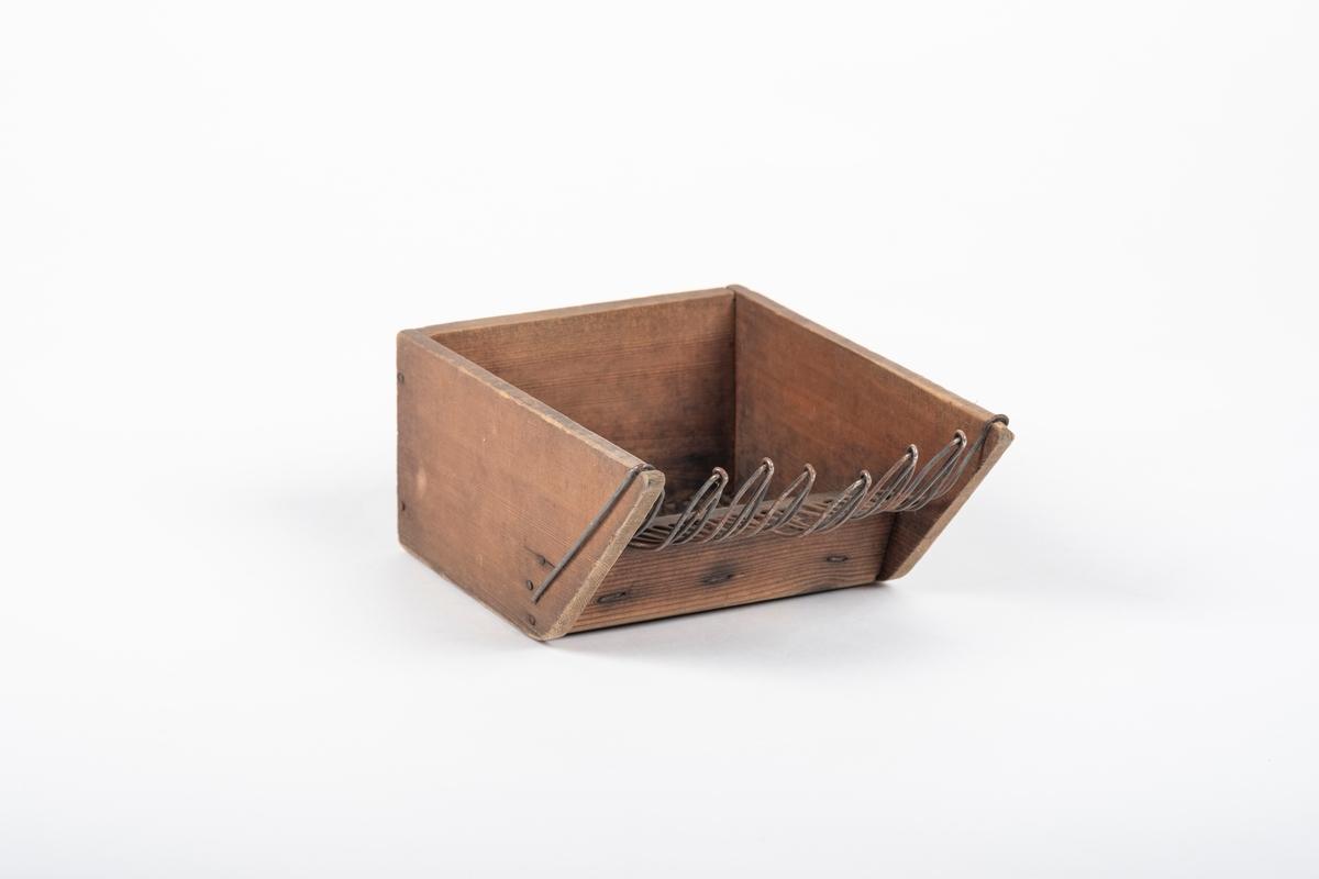 Bærplukkeren består av tre rette treplanker som er spikret til hverandre. Det er to lange og en kort, hvorav de lange er kuttet av skrått slik at overkanten er lenger enn underkanten. 20 tynne metallstenger er festet til den korte planken v.h.a. at en list er spikret på under. De ytterste metallstengene på hver side går over kantene på treverket som en bøyle, for så å være tredd inn i et trestykke i midten av bærpkukkeren. De øvrige metallstengene er festet sammen tre og tre, og går gjennom midtstykket, hvor de bøyes oppover. Foran utgjør stengene butte spisser.