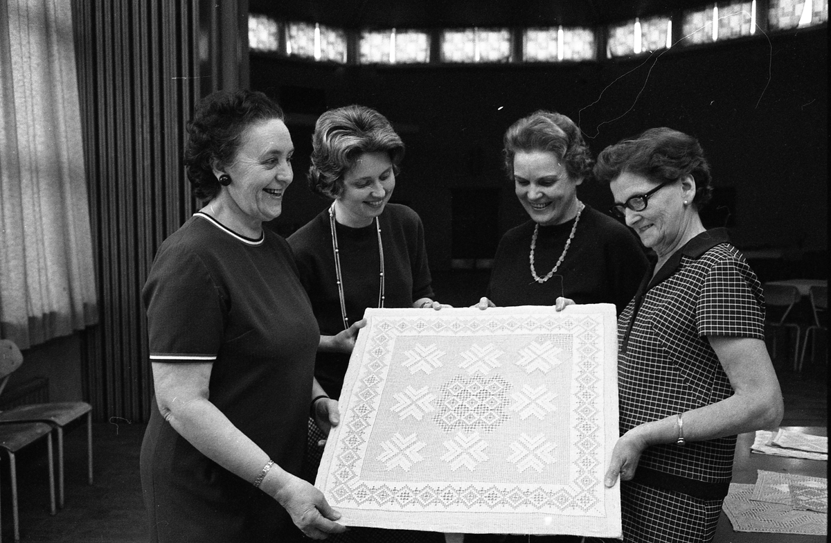 Arbetarnas Bildningsförbunds kursavslutning, fyra kvinnor visar upp en duk i näversöm. Bilden är tagen i Medborgarhuset. Bakom kvinnorna skymtar rotundan.