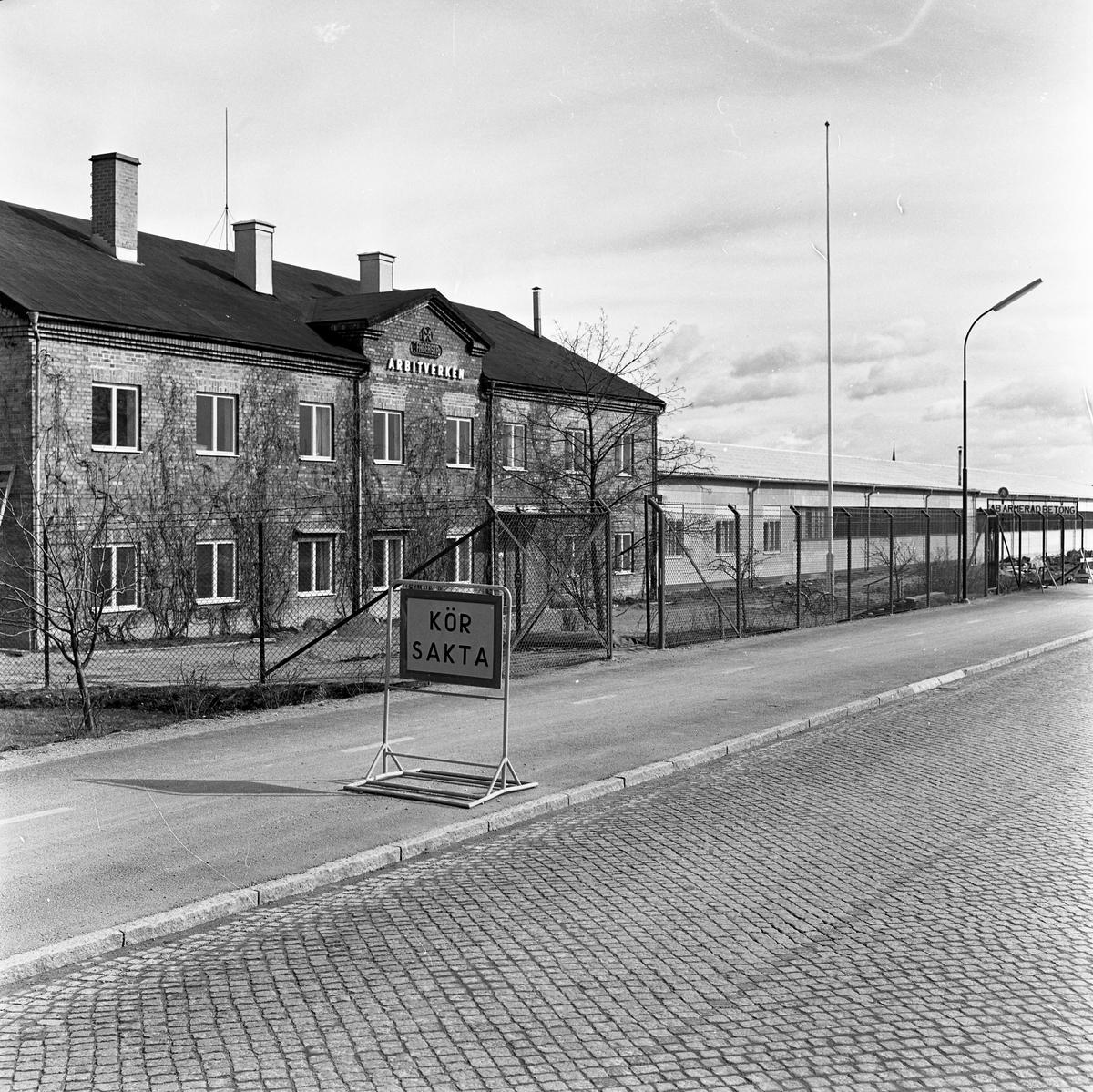 Arbitverkens tegelhus bakom högt staket.