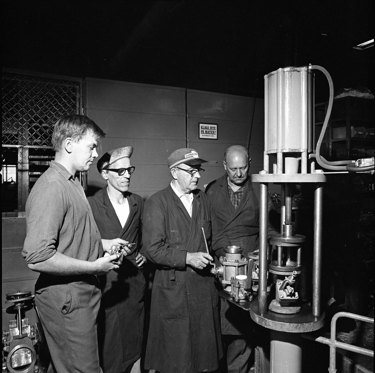 Fyra män i fabrikslokalen på Arboga Armaturfabrik AB. Tre män iklädda arbetsrockar.