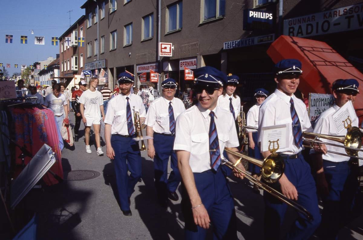 Arboga Blåsorkester marscherar på Nygatan under marknaden Arbogaträffen. Bakre raden, till vänster, går Anders Gelinder, musiklärare. Gatan kantas av människor och marknadsstånd. Till vänster syns Gunnar Karlssons Radio - TV, Berninabutiken och Kajs Tobak.