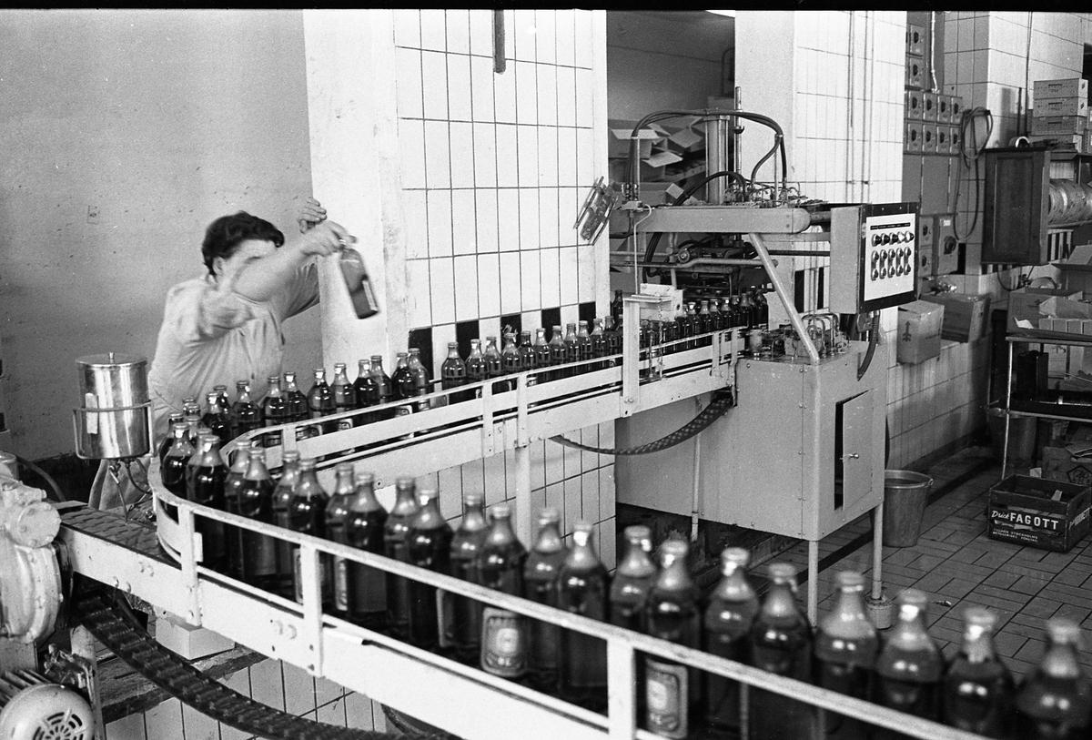 Arboga Bryggeri, interiör. Det är premiär för mellanölet. En person arbetar vid ett löpande band med fyllda ölflaskor. I bakgrunden skymtar tomkartonger på en hylla. Rummets väggar är kaklade.  Anläggningen var färdigbyggd 1899 och verksamheten startade 1 november samma år. 24 oktober 1980 tappades det sista ölet, på bryggeriet. Märket var Dart. Läs om Arboga Bryggeri i hembygdsföreningen Arboga Minnes årsbok 1981