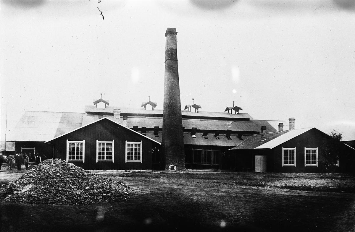 """Arboga Glasbruk, exteriör. Avfotograferat fotografi. Urprunglig fotograf okänd. Träbyggnad med hög, fristående skorsten. I förgrunden ligger en slagghög. Till vänster i bild syns några arbetare.  Uppgifterna om vilket år glasbruket etablerades varierar; 1867, 1870 och 1874 är exempel.  Bolagsordningen, för Arboga Glasbruks AB, stadfästes 1875. Bruket anlades nära hamnen och järnvägen. Buteljer fraktades till Stockholm med lastångaren """"Trögelin"""". På glasbruket tillverkades ca 400 olika sorters flaskor, olika storlekar inräknade. Glasbruket lades ner 1928.  Läs om Arboga Glasbruk i Hembygdsföreningen Arboga Minnes årsböcker 1982 och 2011."""