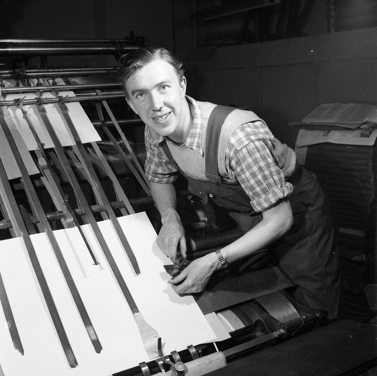 Arboga Tidning, interiör, personal. En man, med snickarbyxor och uppkavlade skjortärmar, arbetar vid en maskin.