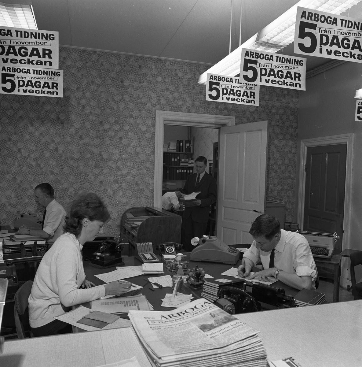 Arboga Tidning, personal och interiör. Tre personer, två män och en kvinna, arbetar i samma kontor. De har var sitt skrivbord. I miljön ses flera telefonapparater, en räknemaskin och en skrivmaskin. I förgrunden ligger en bunt tidningar. I taket hänger skyltar som upplyser om att Arboga Tidning ges ut fem dagar i veckan från och med första november. Mannen längst till höger är Ingemar Eriksson (han är gift med kvinnan på bild 00927). I dörröppningen står tidningens verkställande direktör, Olle Wallström.