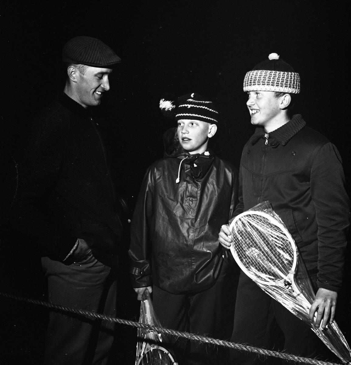 Arboganatta, orienteringstävling. En man och två pojkar, alla i ytterkläder. Pojkarna håller i var sitt badmintonracket. Det är så mörkt att inget annat syns i bilden.