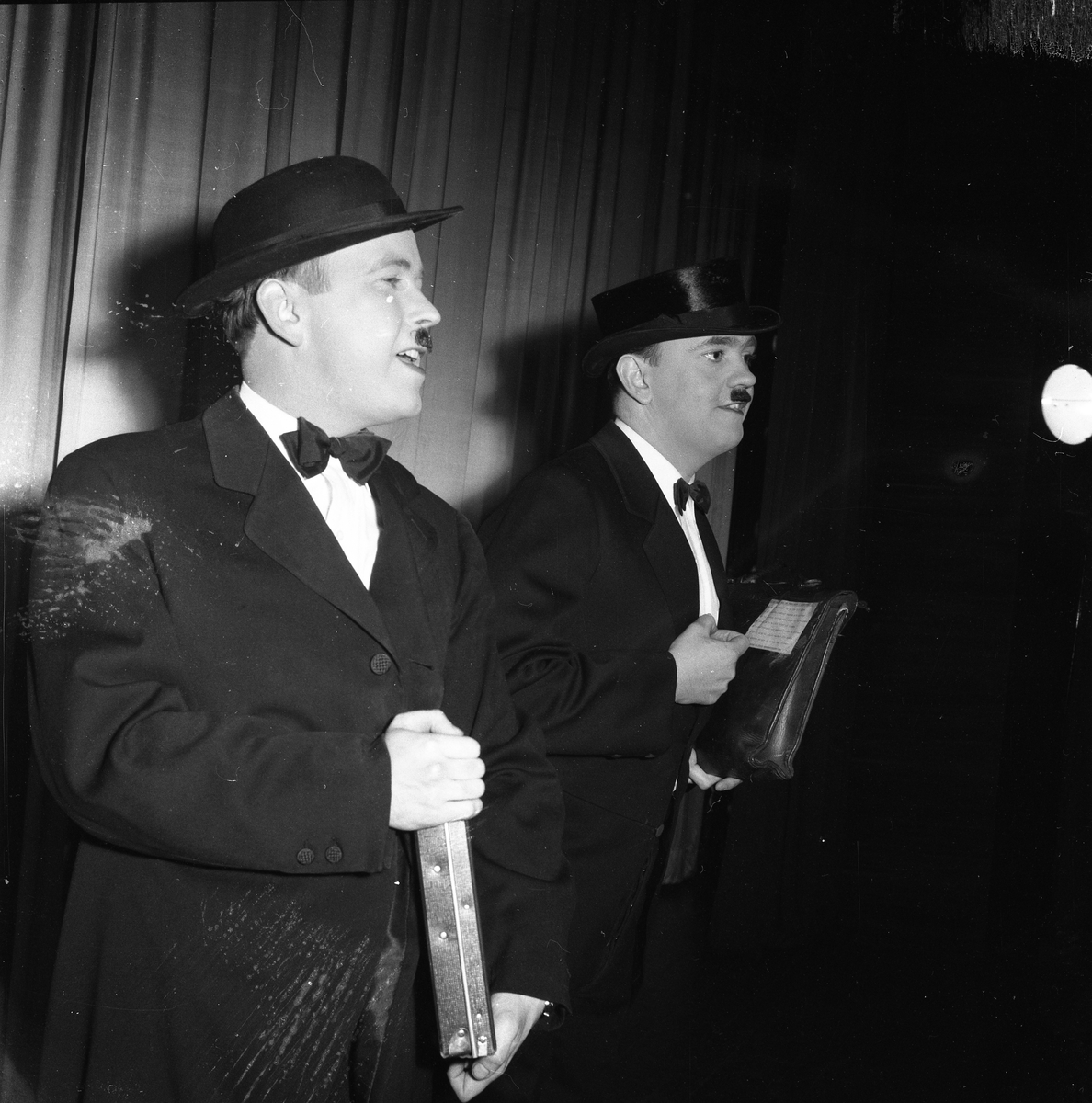 Medlemmarna i Arbogarevyn spelar upp sin Jubileumsrevy. Två herrar på scenen, den högra är Rune Ström. De är klädda i kostym, fluga och hatt. Rune har en portfölj under armen.