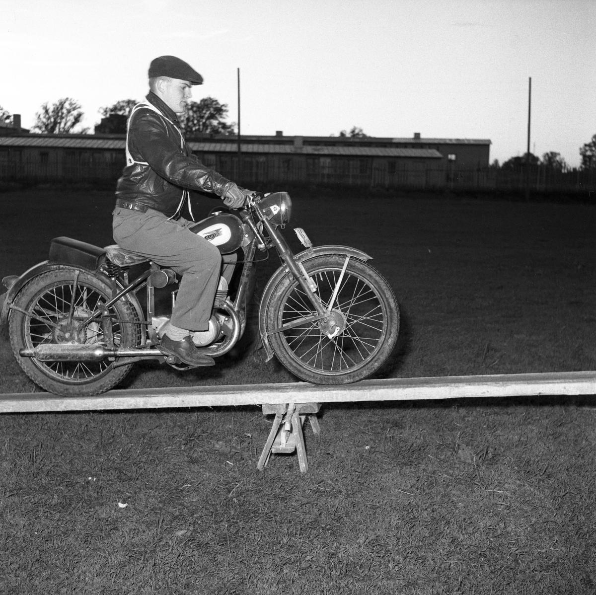 Arbogas Stjärnknutte Balansövning med motorcykel, körning på lutande bräda. Tävling. Mannen är iklädd keps och skinnjacka.
