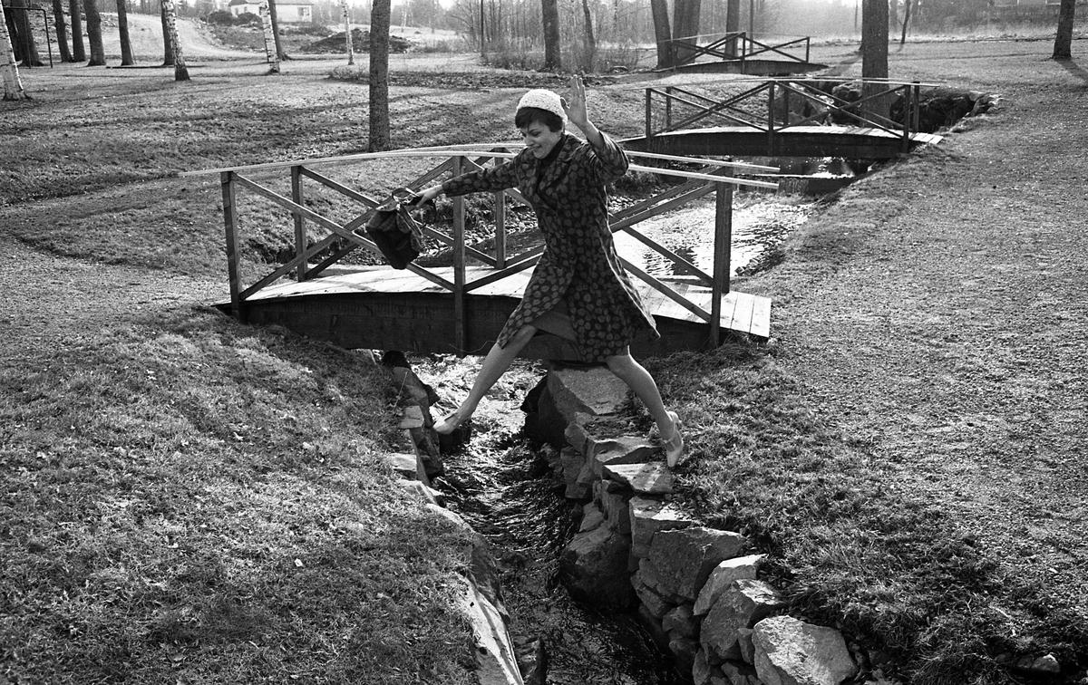 Atlejé Touche. Marianne Rosenqvist visar mode. Mönstrad kappa. Kvinna som hoppar över bäck. Flera broar syns i bakgrunden.