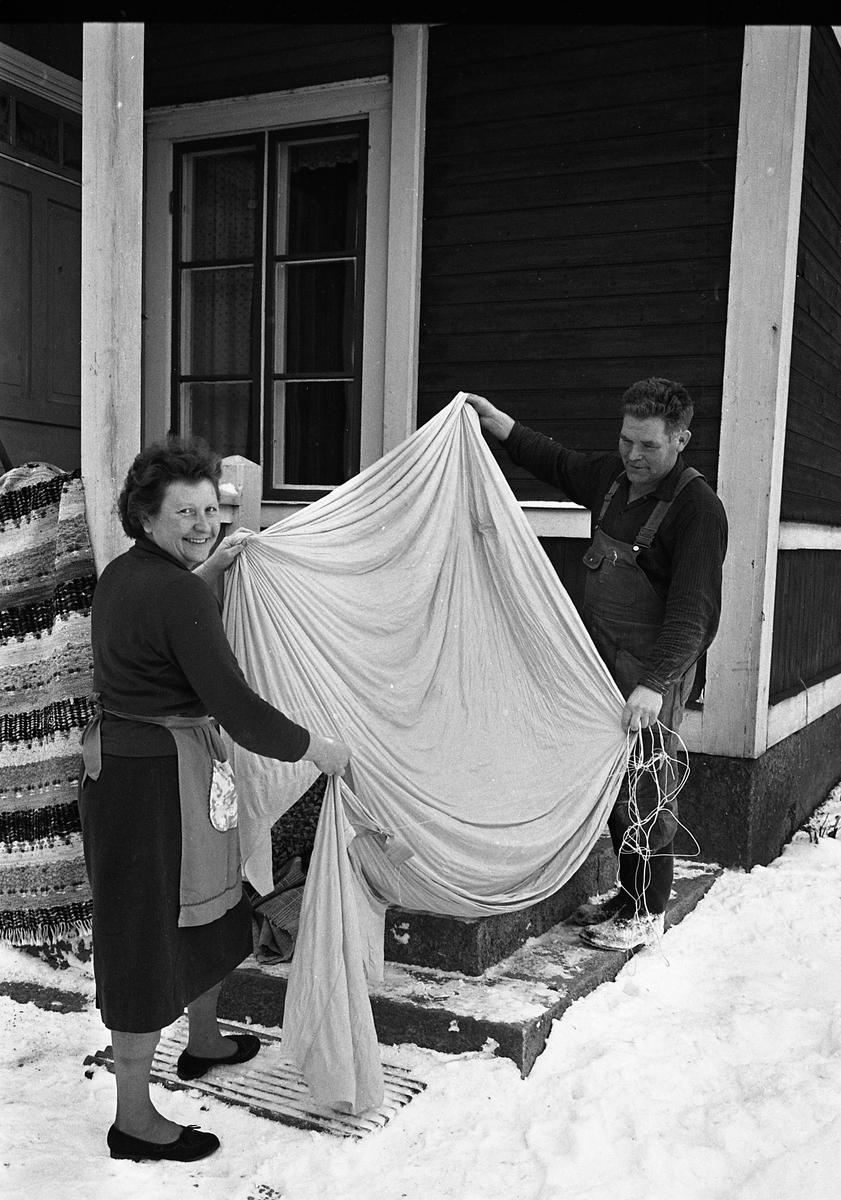 En luftballong har fallit ner hos Signe och Olle Andersson i Tåby, Medåker. Makarna håller i tyget av en ballong. Kvinnan bär midjeförkläde och mannen bär snickarbyxor. De står vid husknuten. Det är snö. En trasmatta hänger på vädring över trappräcket.
