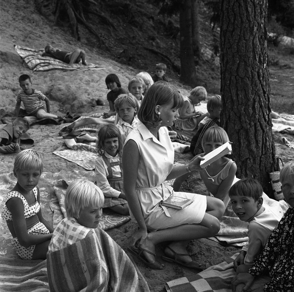 """Barnens Dags koloni i Högsjön. En """"fröken"""" har högläsning. Barnen sitter på filtar och lyssnar."""