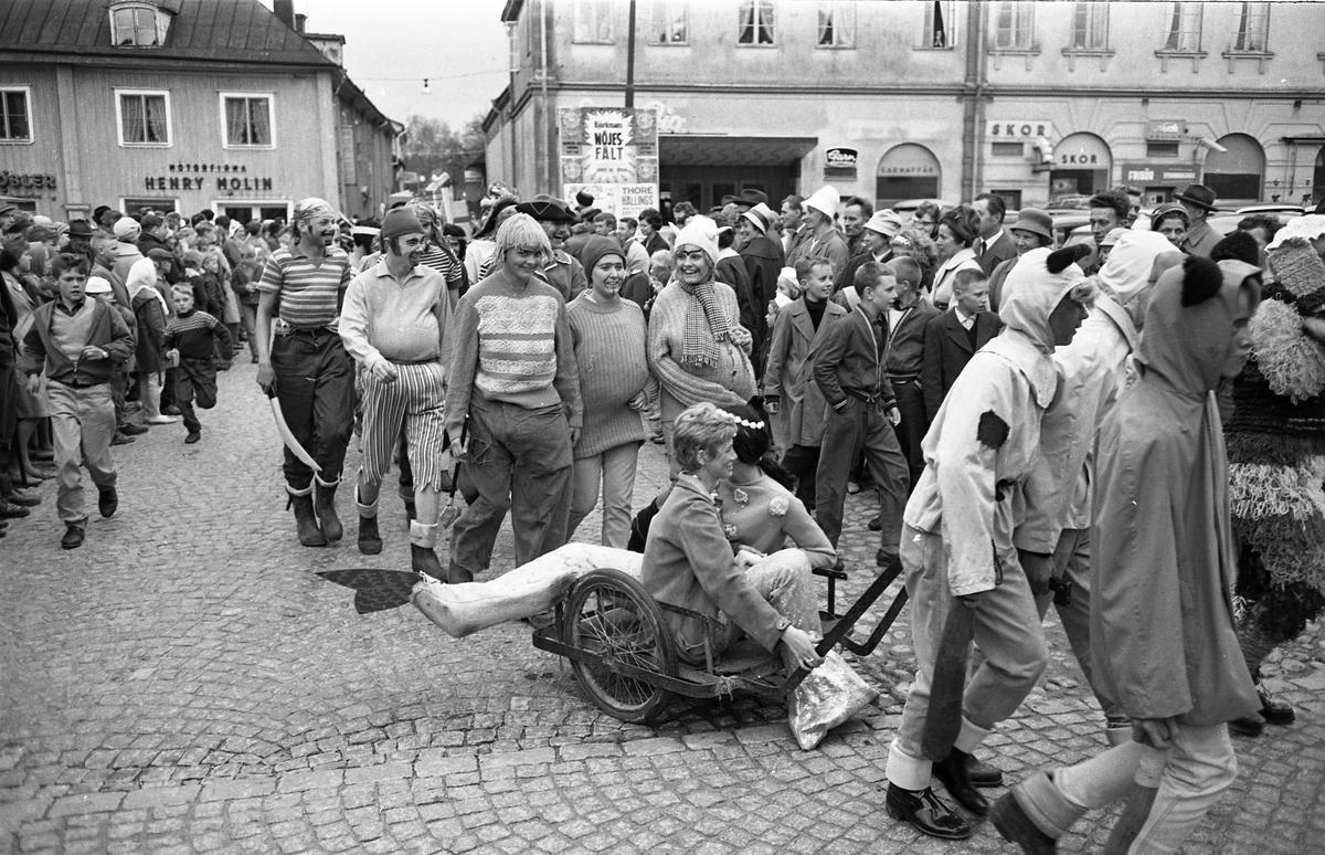 Barnens Dag firas med en parad. Två sjöjungfrur dras på en vagn, följda av en samling sjörövare. En stor publik har samlats på Stora torget för att se på.