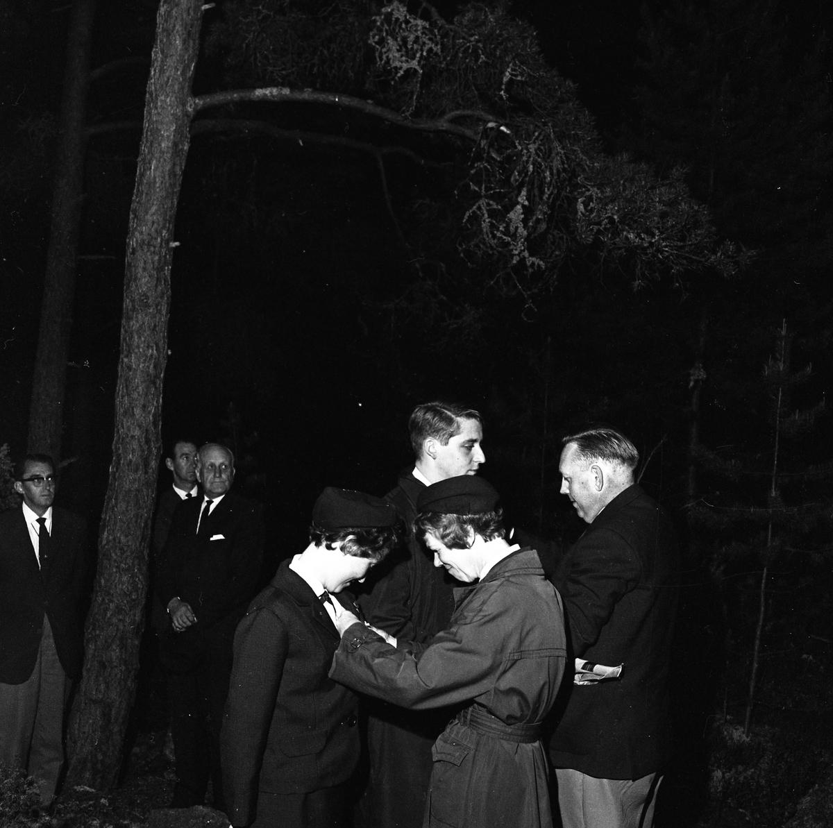 """Belöning till scouter. En kvinna fäster något på rockslaget på en annan kvinna. Tre herrar i slips och kostym tittar på, den tredje från vänster är Harald """"Hajan"""" Larsson. De befinner sig i skogen och det är kväll."""