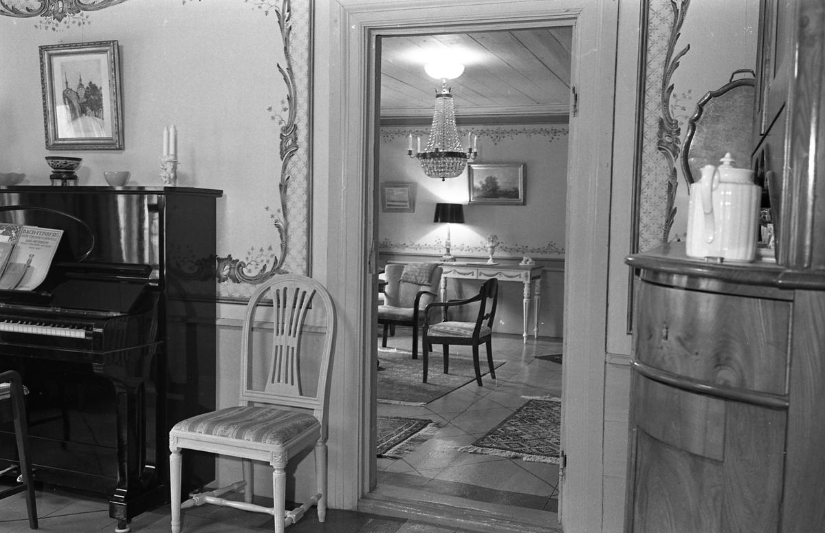 Bostadsinteriör, Crugska gården. Dekorerade väggar. Ett piano till vänster och ett hörnskåp till höger om dörren. I nästa rum ses två karmstolar och en kristallkrona.