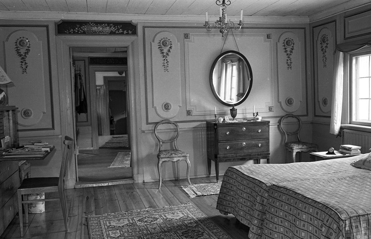 Bostadsinteriör, Crugska gården. Sovrum med två sängar. En chiffonjé med en stol framför, en byrå med en spegel över. Väggarna är dekorerade. Ett fönster. En ljuskrona i taket. Genom dörröppningen kan man se in i flera rum.