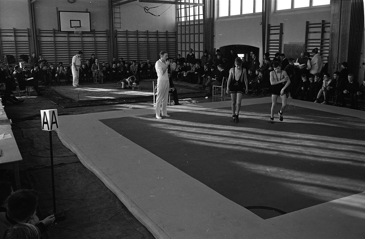 Brottning för ungdomar. Matcher på två mattor samtidigt. Närmast kameran är två kombattanter på väg till sin match. Tävlingarna pågår i en gymnastiksal. Publiken sitter runt väggarna.