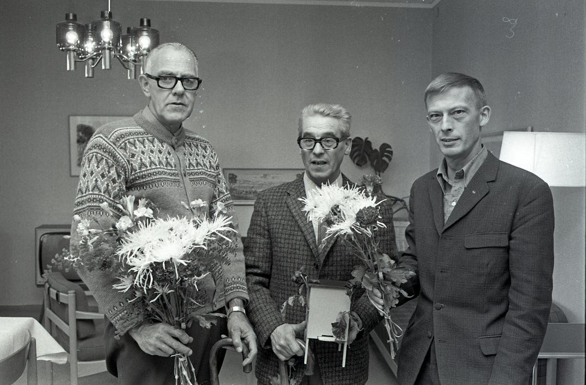 Två män går i pension och avtackas med blommor. Platsen är möjligen ett personalrum på CVA Centrala Verkstaden Arboga