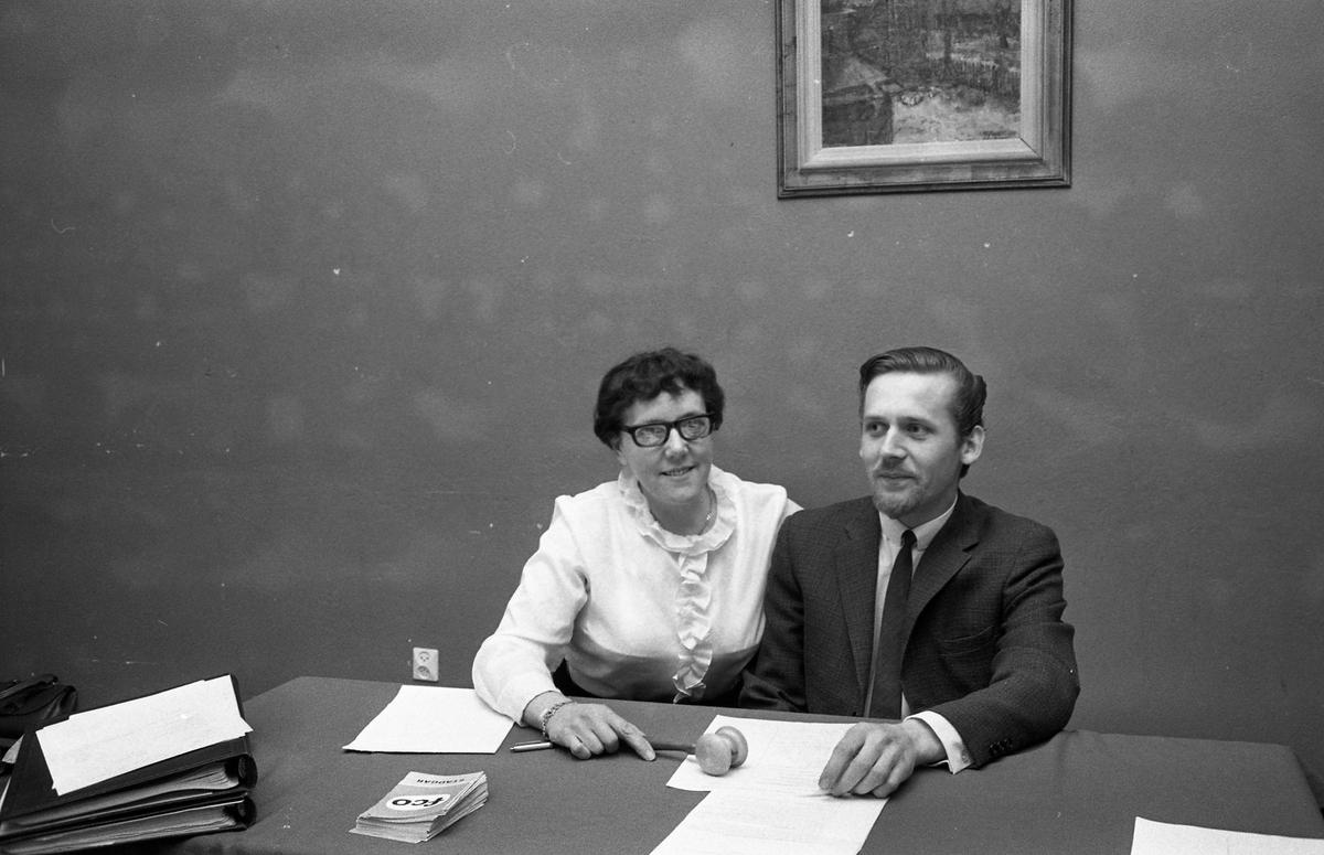 FCO har årsmöte. Anna-Lisa Isaksson och Birger Hagström sitter vid ett bord. En ordförandeklubba ligger framför dem. Pärmar och broschyrer ses också på bordet.