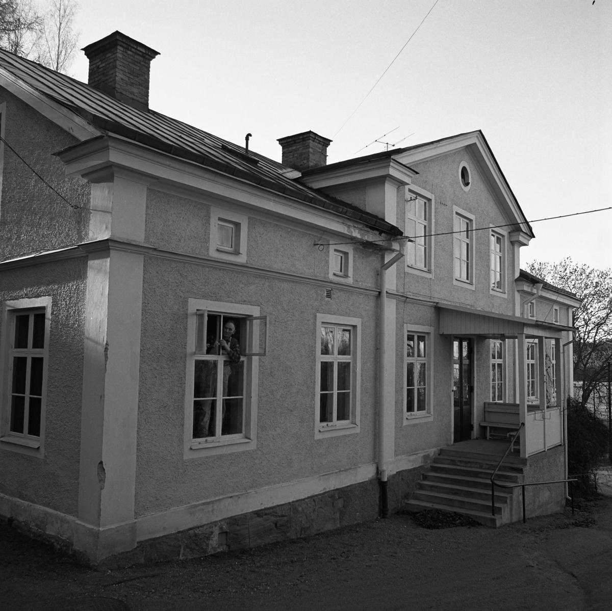 Gamla ålderdomshemmet rustas. En man står i fönstret och skrapar färg. Exteriör. (Omgjort till dagis/förskolan Sörgården, 1980-talet)