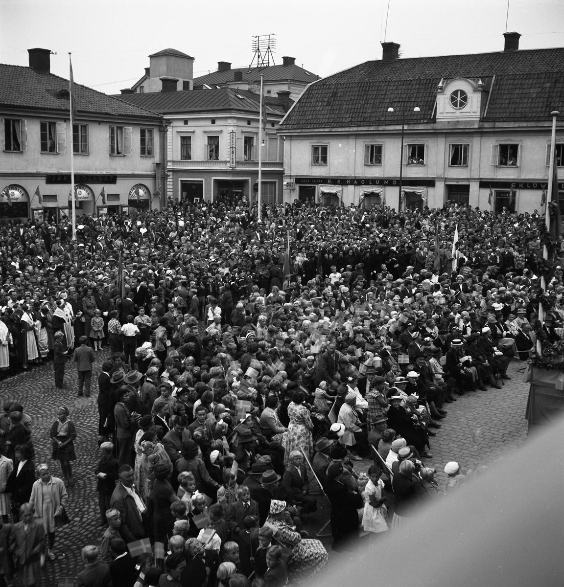Publik på Stora torget. Skolbarn med flaggor, Frälsningsarmén, unga och gamla har samlats för att se och höra kung Gustaf Vl Adolf. Han gästar Arboga under sin Eriksgata. Han står på den uppbyggda scenen till höger, strax utanför bild. Järnbolaget, Specerier, Haglunds Guld och Eklöws bosättning ses i bakgrunden. För värdskapet svarade stadsfullmäktiges ordförande Jonas Carlsson och kommunalborgmästare Danliel Ekelund. Den organisationskommitté som ansvarade för arrangemangen, hade hos drätselkammaren begärt en summa av 3000 kronor för att täcka kostnaderna vid kungabesöket. Beloppet beviljades.  Tiden för kungens besök var beräknad till 130 minuter.