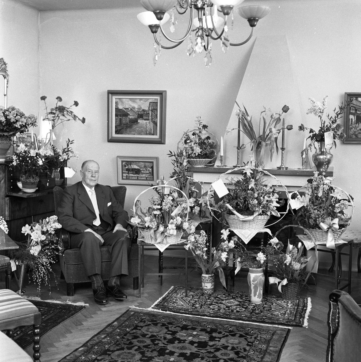 Hemma hos byggmästare Johan Sörén på bemärkelsedagen En man sitter i en fåtölj i sitt vardagsrum. På chiffonjén står blommor i vaser, på spiselkransen och på golvet står korgar och vaser med blomsteruppsättningar och buketter.