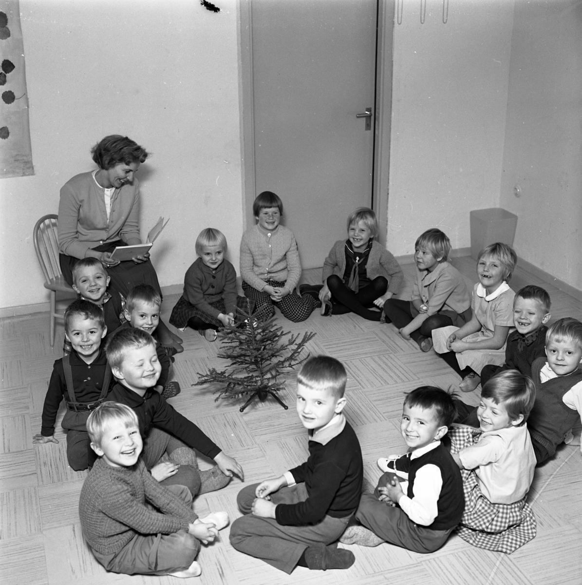HSB´s barnträdgård. Sagostund. Fröken läser ur en bok och barnen sitter i ring på golvet. Mitt i ringen står en liten julgran. (HSB betyder Hyresgästernas sparkasse- och byggnadsförening)