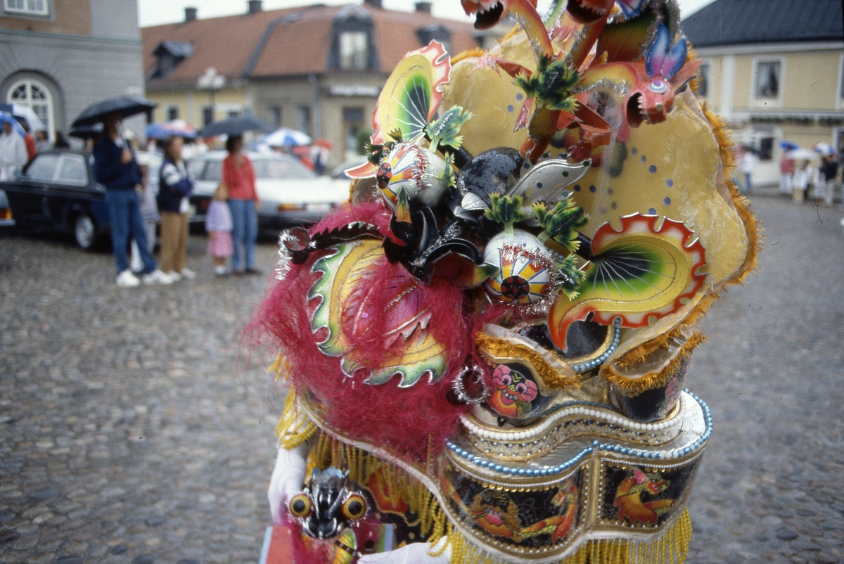 Arbogakarnevalen. Utklädd dansare på Stora torget. I bakgrunden står en liten publik, under paraply, och ser på.