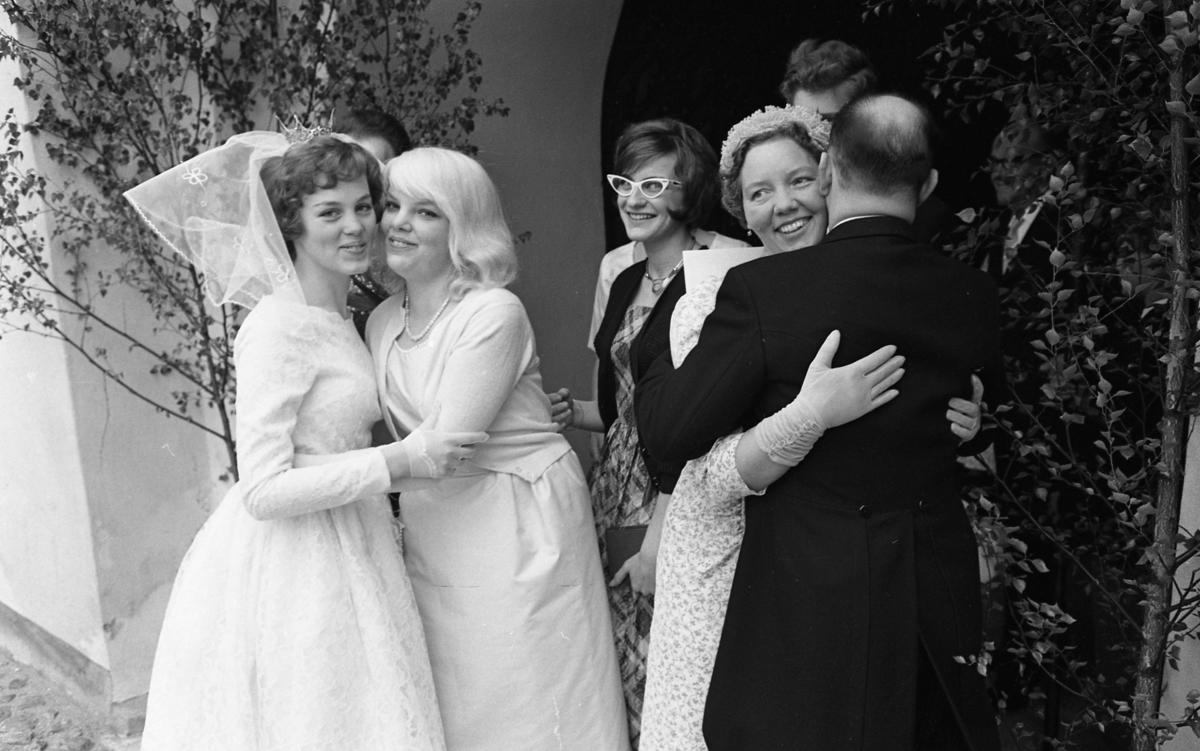 Systrarna Einarsson; Margareta och Birgitta, kramas utanför kyrkporten. Margareta har just gift sig med Rune Ström (mannen i frack, med ryggen mot fotografen). Rune får en kram av svärmor; Ingrid Pettersson. Genom kyrkporten kommer Harriet Malmberg Svanberg. (Birgitta Einarsson gifte sig senare och fick namnet Sparv)