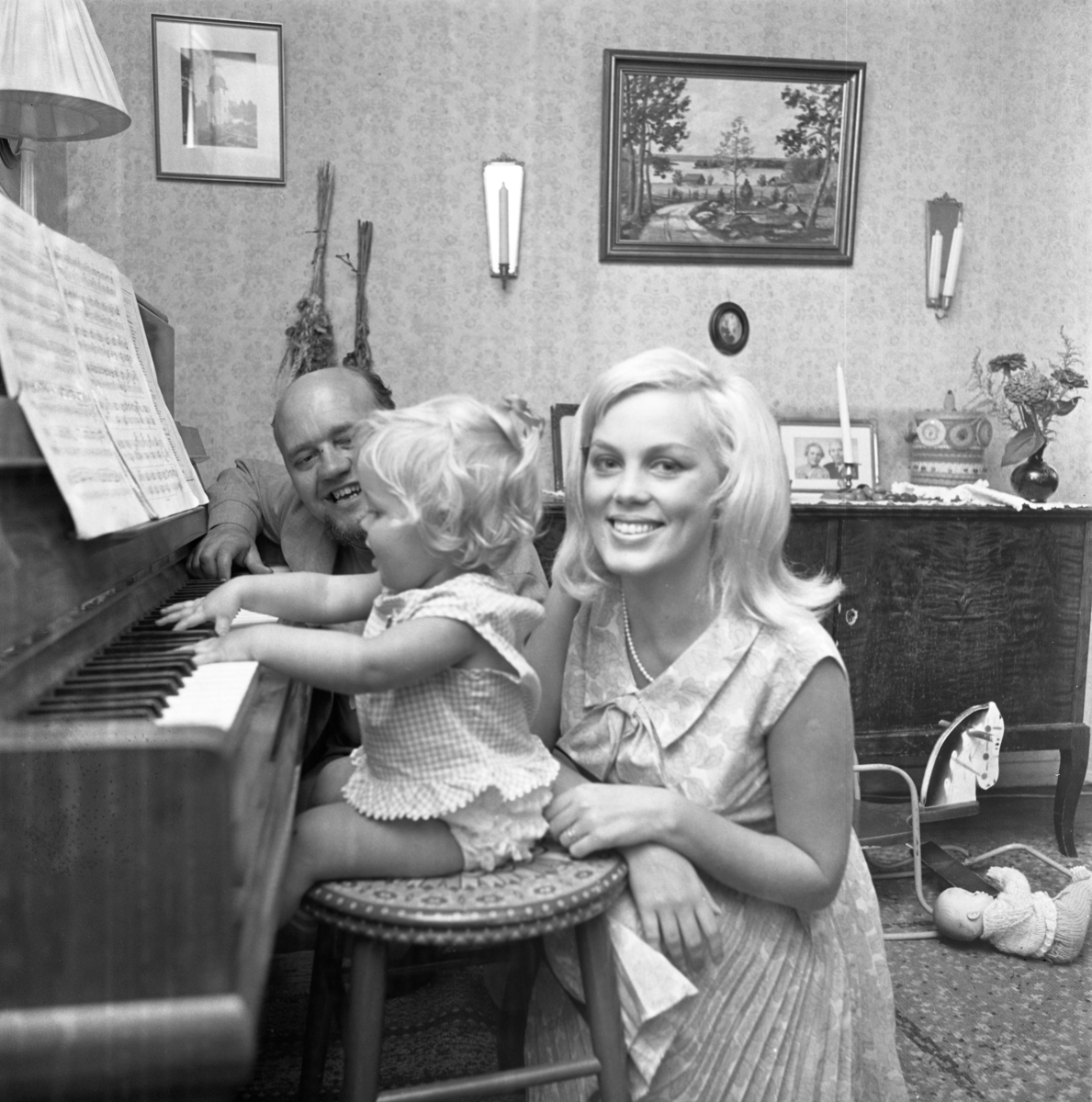 """Familjen Ström vid pianot hemma hos Ingrid och Einar Pettersson. Pappa Rune, mamma Margareta och dottern Fredrika """"Fia"""" hälsar på hos Margaretas föräldrar."""