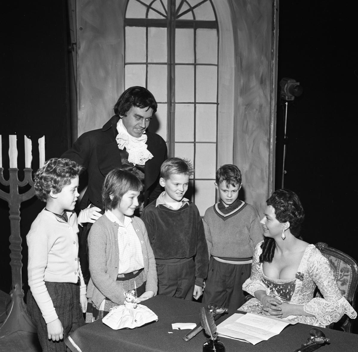 Skolteater på Folkan/Medborgarhuset Två skådespelare har bjudit upp fyra barn på scenen. Längst till vänster står Birgitta. Skådespelarna är en man och en kvinna. Kvinnan, klädd i djupt ringad klänning, sitter vid ett bord. På bordet finns bland annat en gåspenna och två pistoler.