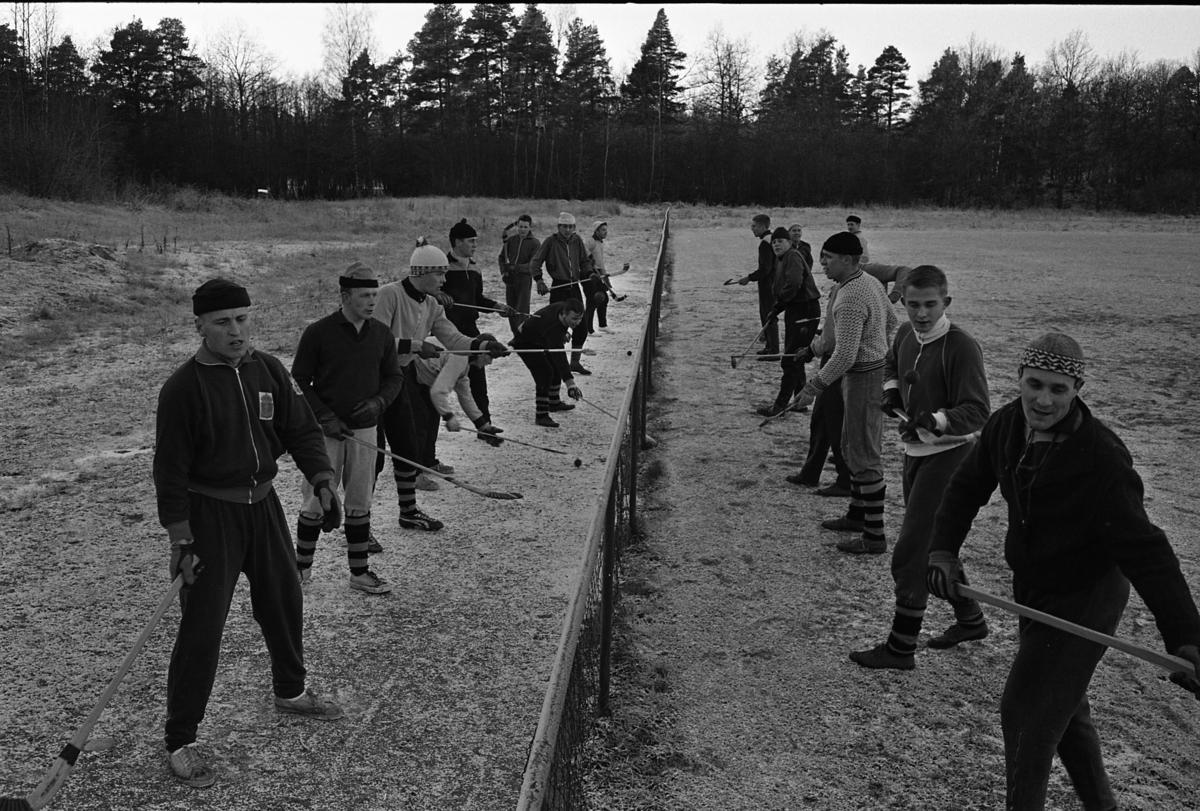 Arboga Södra IF har bandyträning. Spelarna har övningar utomhus, på ett fält. Alla har klubbor i händerna.