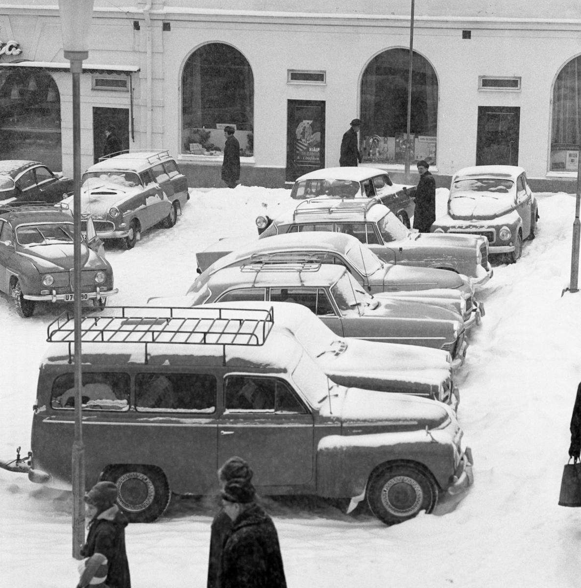 Det är mycket snö och svårt att parkera på Stora torget. Bilarna står tätt. Människorna är rejält påklädda. I bakgrunden ses Lundborgska fastigheten med café Saga