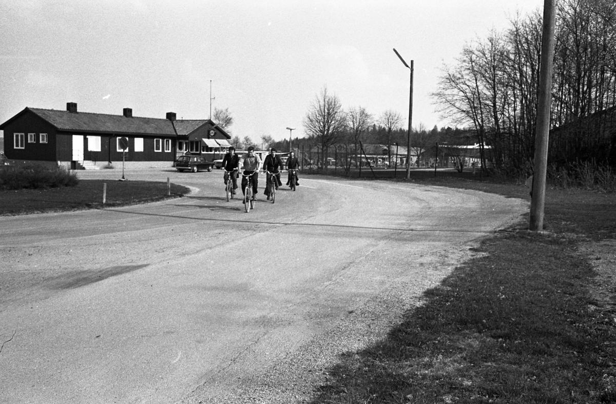 Arbetsdagen är slut på CVA, Centrala Verkstaden Arboga. Några män är på väg hem på sina cyklar. I bakgrunden ses byggnaden där vakten sitter. Två bilar ska passera grinden.