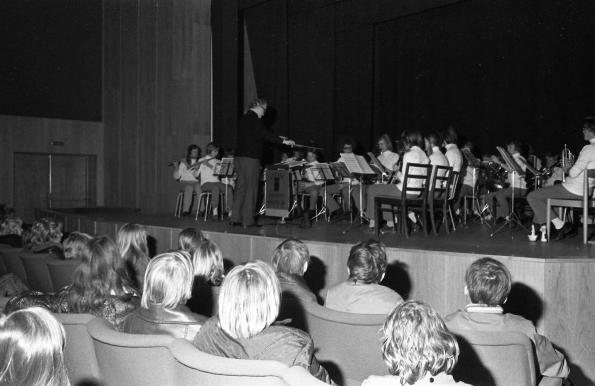 Ungdomsmusikkåren underhåller från scenen i Medborgarhuset. Dirigent är Karl-Axel Göransson. Publiken består av ungdomar.