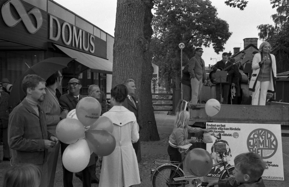 Socialdemoktraterna håller valmöte utanför Domus. Per-Olov Nilsson håller i ballonger, i bakgrunden ses Gustav Danielsson och Nils Brodin. Berit Oscarsson står på ett lastbilsflak och talar över Nytorget. Bakom henne ses en liten orkester.