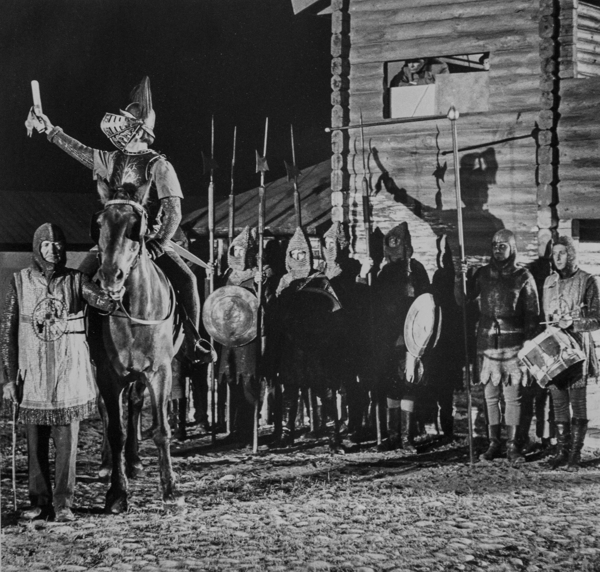 """En scen ur skådespelet Giv oss fred. En riddare, i rustning, till häst. Män med sköldar och hillebarder. Bredvid hästen står kusken Gustav Jansson. """"Giv oss fred"""", även kallat """"Arbogaspelet"""", är ett teaterstycke skrivet av Rune Lindström 1961. Handlingen, som är inspirerad av Arbogas klosterhistoria, är förlagt till början av 1500-talet. Uruppförandet skedde den 11 augusti 1962 och Rune Lindström spelade Engelbrekt Gertsson. Lions Club i Arboga stod för arrangemanget. Föreställningarna regnade bort och det blev ett stort ekonomiskt bakslag för föreningen. Spelet har framförts igen; 1987, 1988, 2012 och 2015 av medlemmar i """"Bygdespelets Vänner""""."""