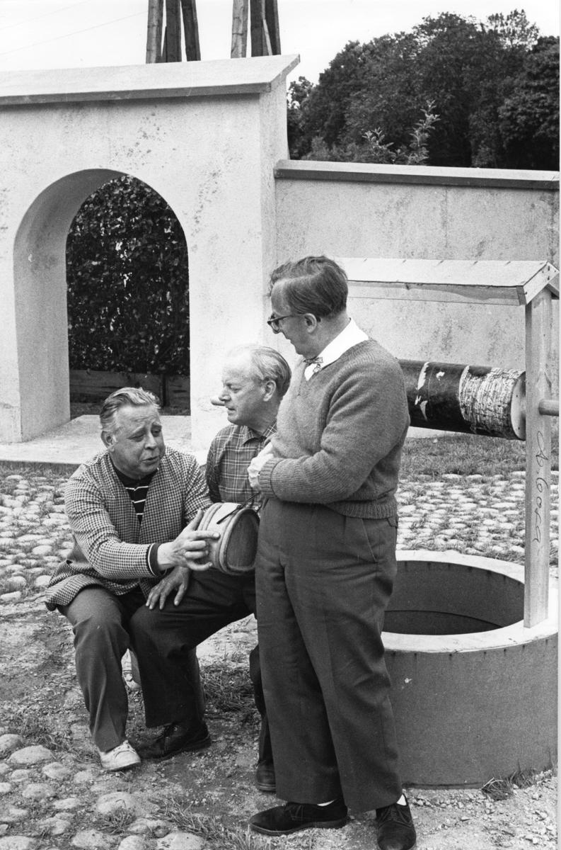 """Repetition av skådespelet """"Giv oss fred"""". Till vänster Rune Lindström. Tre män är samlade vid brunnen. """"Giv oss fred"""", även kallat """"Arbogaspelet"""", är ett teaterstycke skrivet av Rune Lindström 1961. Handlingen, som är inspirerad av Arbogas klosterhistoria, är förlagt till början av 1500-talet. Uruppförandet skedde den 11 augusti 1962 och Rune Lindström spelade Engelbrekt Gertsson. Lions Club i Arboga stod för arrangemanget. Föreställningarna regnade bort och det blev ett stort ekonomiskt bakslag för föreningen. Spelet har framförts igen; 1987, 1988, 2012 och 2015 av medlemmar i """"Bygdespelets Vänner"""". Fler bilder finns i Reinhold Carlssons bok """"Arboga objektivt sett""""."""