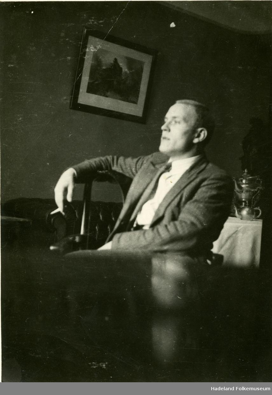 En mann sitter avslappet med en røyk i hånda.
