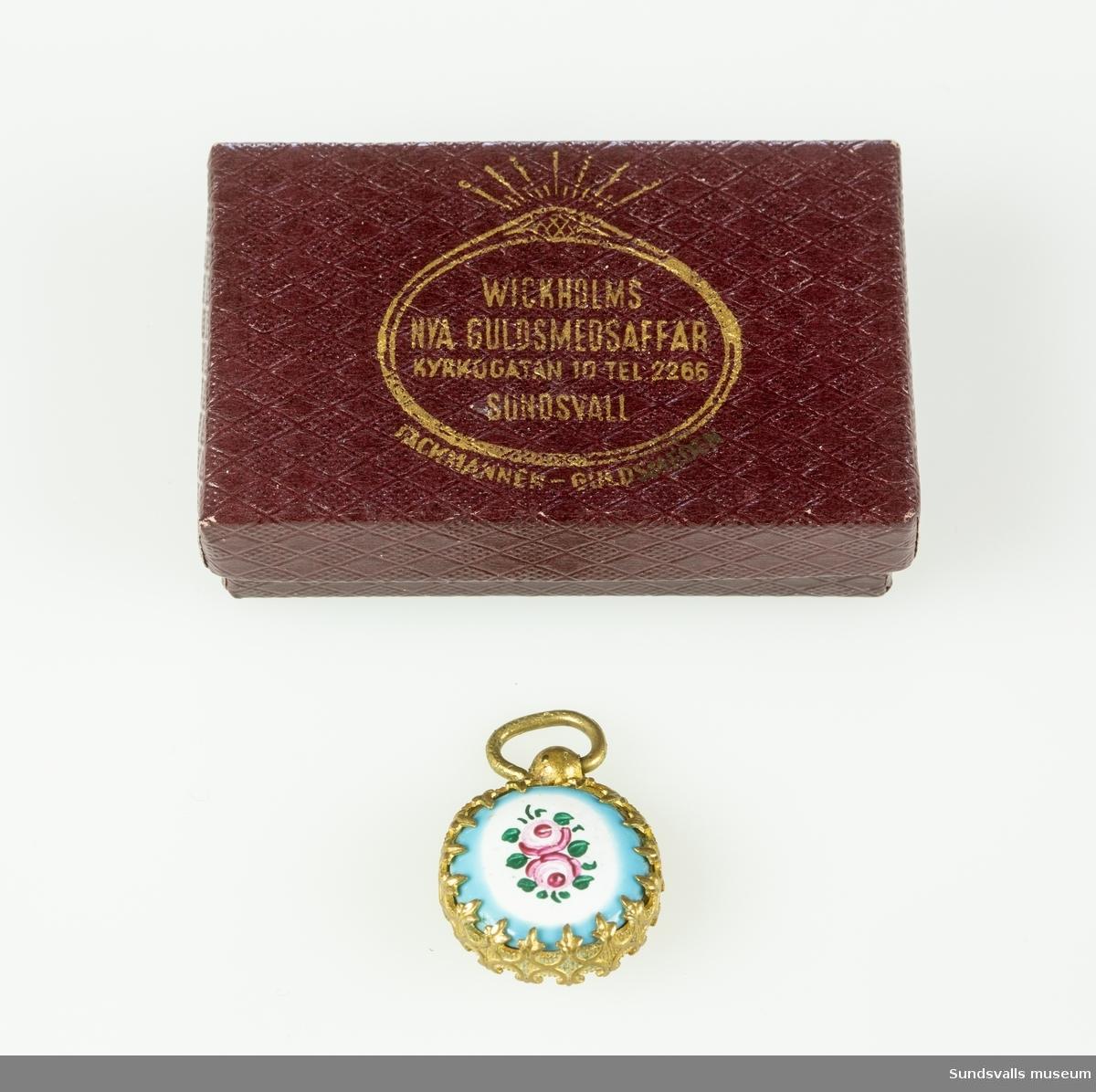 SuM 4754:1-2 smycke med ask. SuM 4754:1 smycke föreställande ett fickur i miniatyr med vit, rund urtavla med tryckta romerska siffror och visare. Plastglas. På baksidan är smycket dekorerat med två rosa rosor på vit botten med turkos kant. Smyckets diameter är 1,6 cm. SuM 4754:2 pappask, mörkt blåröd med pressat rutmönster. Guldtryck på locket 'Wickholms Nya Guldsmedsaffär, Kyrkogatan 10, Tel. 2266 Sundsvall, Fackmannen - Guldsmeden'.