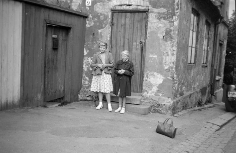 Bildet er fra Johannesgata. Jeg Wenche Olsen bodde med mamma og pappa der, fram til ca. april-mai 1945. Jeg var ca. 2 år. Det var kun et rom med strøm, men ikke innlagt vann. Bildet er tatt før Bodil Rødberg Larsen og jeg skulle reise på feriekolonien. Vi skulle være på forskjellige steder. Koloniene var på Hadeland. Veska som står i forgrunn er min. Tror Bodil er 8-9 år og jeg 9-10 år. Vi var pene i tøyet fordi det var reisetøy, som ble hengt bort under oppholdet.