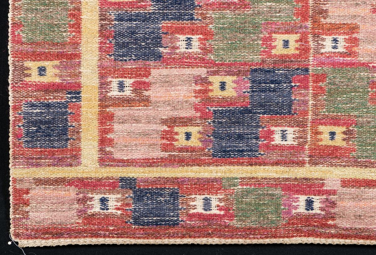 """Duk, inplockat mönster, """"Röda Lövendal"""". Röllakan och inplockat mönster. Varp och väft oblekt lingarn. Mönsterformerna i mycket nyanserat rött, i blekrött, blått och grönt. Före 1928.  Varp: 4 tr/cm            Inslag: ca 6/cm Varp grågult, oblekt lingarn, inslag vitt och grågult, oblekt lingarn, mörkblått, blågrått, blårött, rödblått, mörkt rödblått, ljust gulrött, gröngult, gröngrått, grönt, gulgrönt, gult, rött, ljusrött, grått, rödgrått och ljusbrunt ullgarn, troligen 1 tr, inplock på linnebotten, MMF-teknik. Mittpartiet kvadrater i olika nyanser rött, blått och grönt som är placerade i viggform, inuti en del kvadrater mindre kvadrater i gult eller grågult, oblekt med en blå rektangel i mitten, mittpartiet delas på mitten av en melerad grågul, oblekt/gul rand, runt omkring mittpartiet en fyrkantig bård i gult, ytterst en fyrkantig bård med kvadrater i ljust gulrött, grönt, gulgrönt och mörkblått, däremellan mindre kvadrater i gulgrått, oblekt eller gult med en rektangel i mörkblått i mitten, botten i olika nyanser rött. Vävnaden avslutas med s.k. orientalisk fläta.  Ett ca 10,5 cm brett vitt tygstycke i tuskaft, bomull, fastsydd på avigsidan längs ena kortsidan s.k. kanal."""