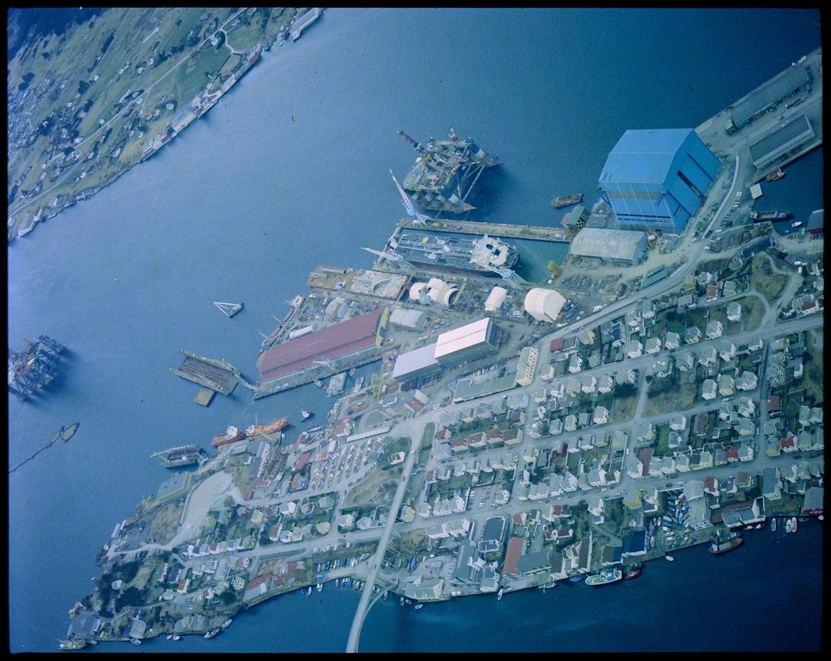 """Risøy med Haugesund Mekaniske Verksted ut mot Karmsundet og Karmøy i bakgrunnen. Et skip ligger i tørrdokk med riggen """"Ocean Liberator"""" utenfor. En rigg er ankret opp ved Storasundskjer."""