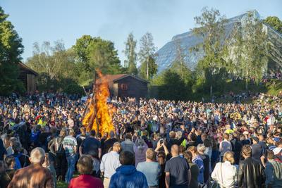 Sankthansbålet brenner midt på en slette fylt med glade tilskuere, de gamle husene på Hedmarkstunet og Hamardomen vises i bakgrunnen.