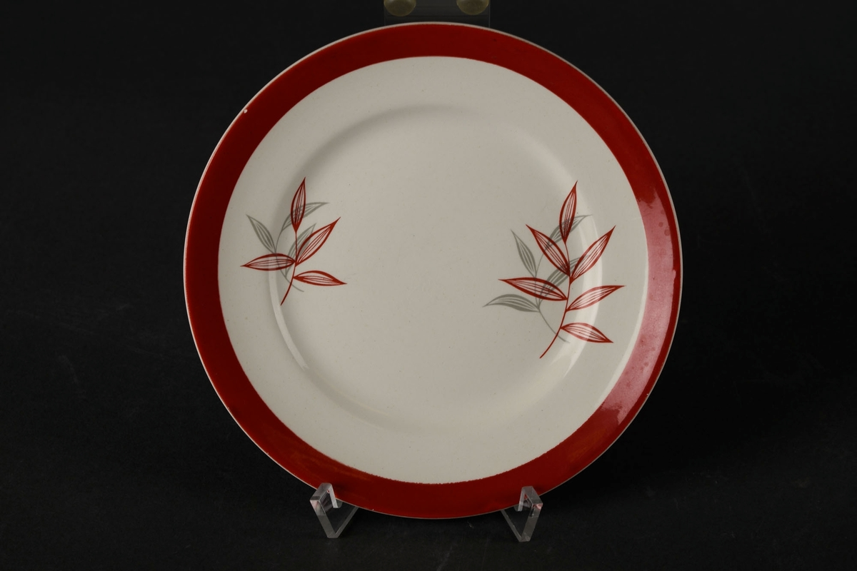 Hvitt asjett dekorert med en rød sirkel, og to røde og to grå planter på hver sin side av midten.