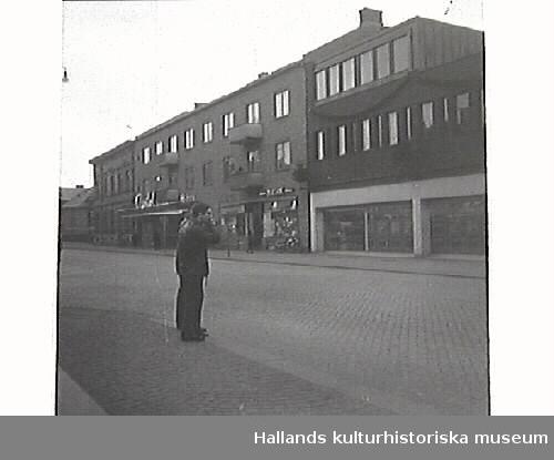 """Stadsvy från Västra Vallgatan. Bilden tagen mot väster och visar södra delen av Domus samt biografen Capitol .  Tidningsartikel: """"De här herrarna som är betänkta på att kila 'raka spåret' över till Domus riskerar att bli bötfällda om de inte begagnar övergångsstället ca 20 meter längre bort"""". Publicerat i Hallandsposten 1967-01-05. Artikel i samband med bilden 6/3 1967."""