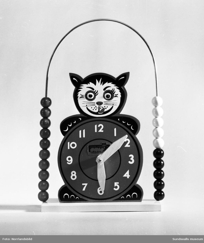 Olika leksaker fotograferade för varuhuset Dahlmans julannonsering 1959. Bland annat en klocka med kulram, docka, bilar i trä och plåt samt en hund i trä.