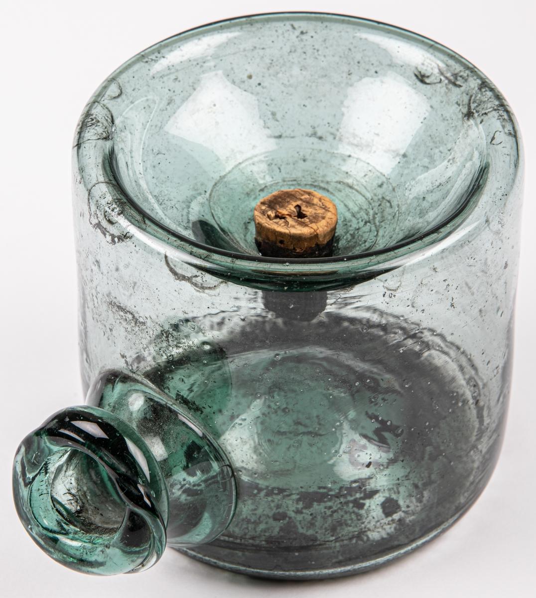 Bläckhorn av glas, grönt, runt med öppen pip åt ena sidan. Liten kork i hål i fördjupning ovanpå.