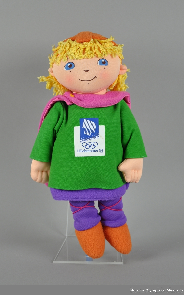 Tekstildukke som forestiller maksoten Håkon. Dukket har gult hår, lysebrun lue, rosa cape, grønn genser med emblemet for Lillehammer '94, lilla underkjole og strømper, og lysebrune sko.
